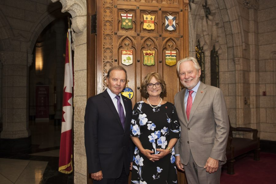 Senator Julie Miville-Dechêne is greeted by Senator Serge Joyal (left) and Senator Peter Harder (right).