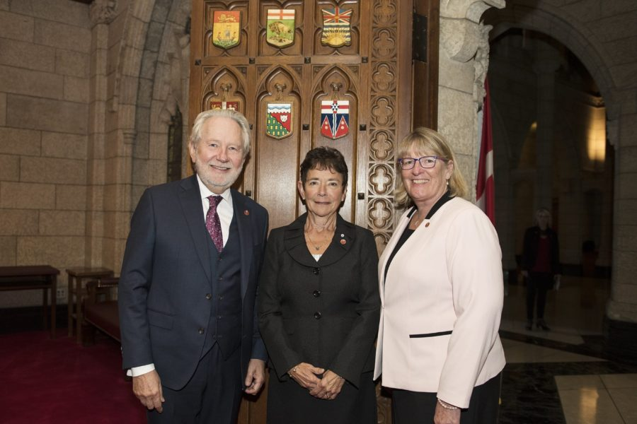 Senator Peter Harder (left) and Senator Gwen Boniface (right) welcome new independent Senator Beverly Busson (centre) to the Red Chamber for the first time on Sept. 27, 2018.